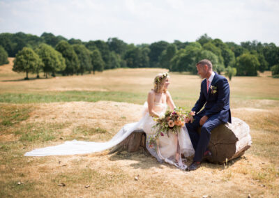 Bride and groom in Beckenham Place Park sitting on log