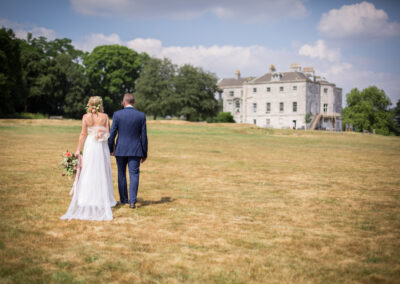 Bride and groom walking shot at Beckenham Place Park with Beckenham Place Mansion in the background