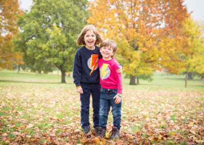 Siblings cuddling in the park in autumn taken by Beckenham photographer