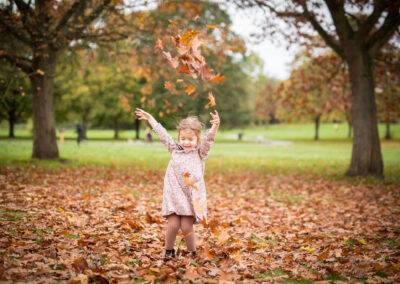 Girl playing in the leaves on family photoshoot in London